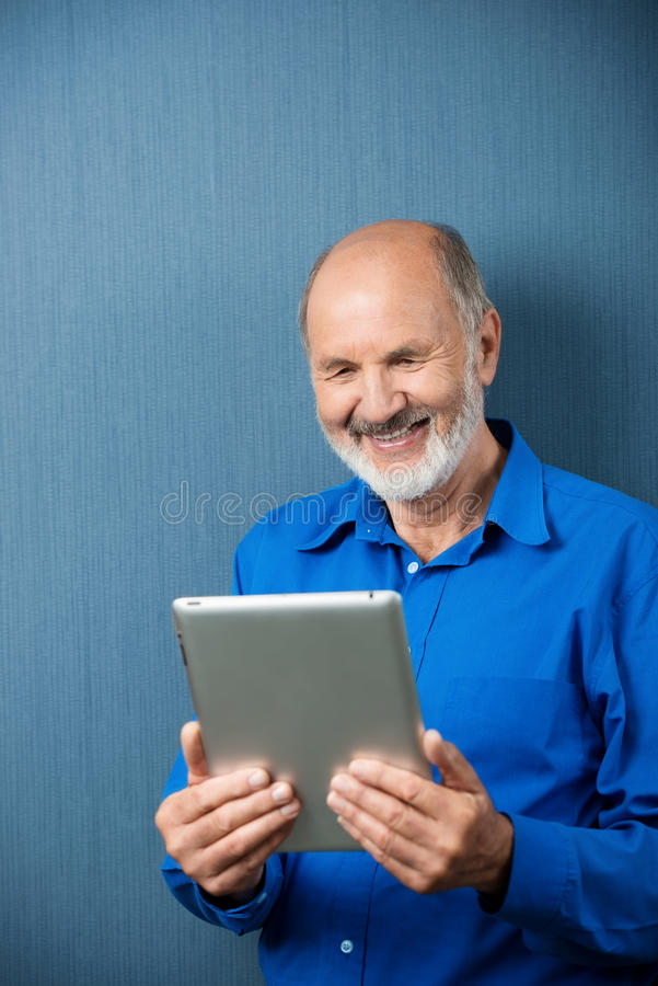 Elderly man laughing at information on his tablet stock image