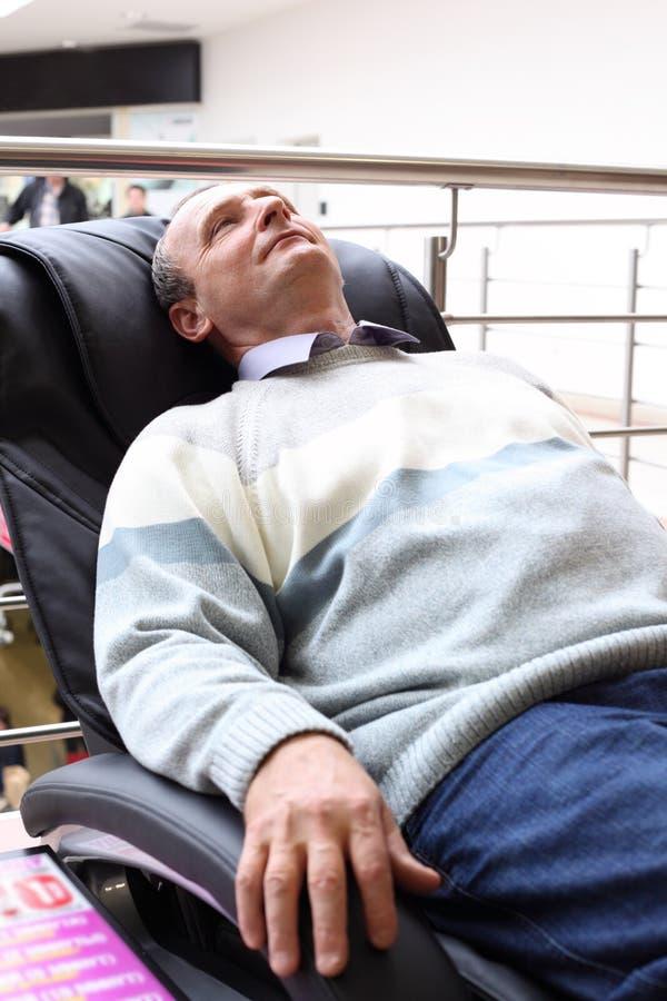 Elderly man lies in massage armchair royalty free stock photos