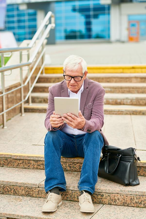 Aged entrepreneur with tablet on steps royalty free stock photos