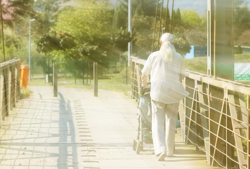 An elderly man with long, gray, athletic build hair walks with a child in a pram over a bridge. Activity in old age. Lessons for royalty free stock photo