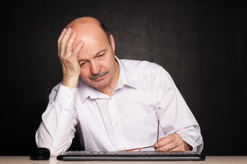 Elderly man looking away thoughtfully, pondering the problem or. Fall asleep at work fatigue and boredom stock photography