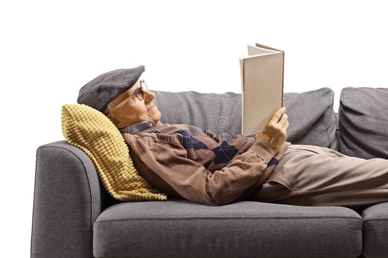 Elderly man lying on a couch and reading a book stock photography