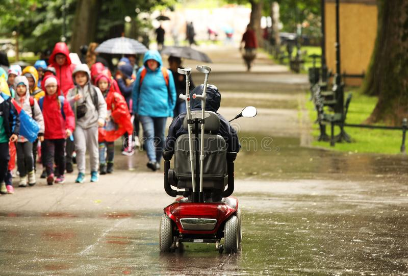 An elderly man in a mechanical wheelchair is passing by the alee of the park past a passing group of children. Sympathy and help. To people in need. Active and stock images