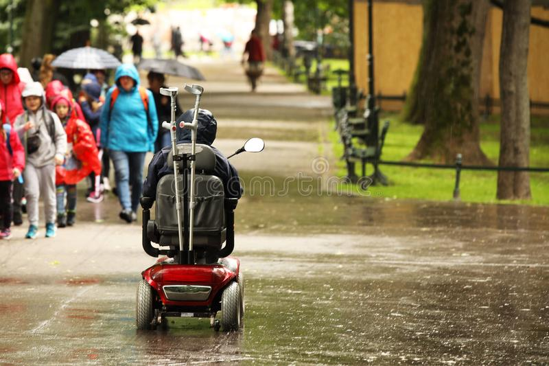 An elderly man in a mechanical wheelchair is passing by the alee of the park past a passing group of children. Sympathy and help. To people in need. Active and royalty free stock photos
