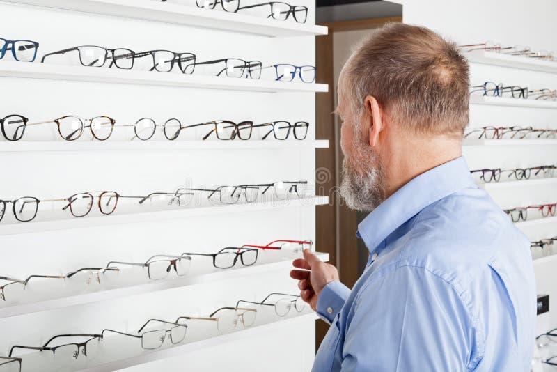 Elderly man in optics store royalty free stock photo