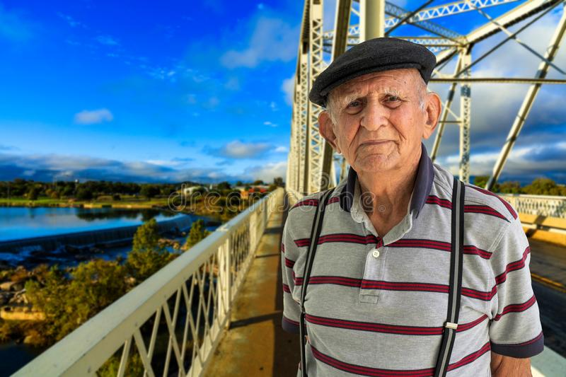 Elderly Man Outdoors. Elderly 80 plus year old man outdoor portrait standing in the road with a vintage bridge in the background stock image