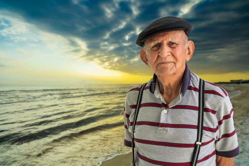 Elderly Man Outdoors. Elderly 80 plus year old man outdoor portrait enjoying the beach at sunset stock photo