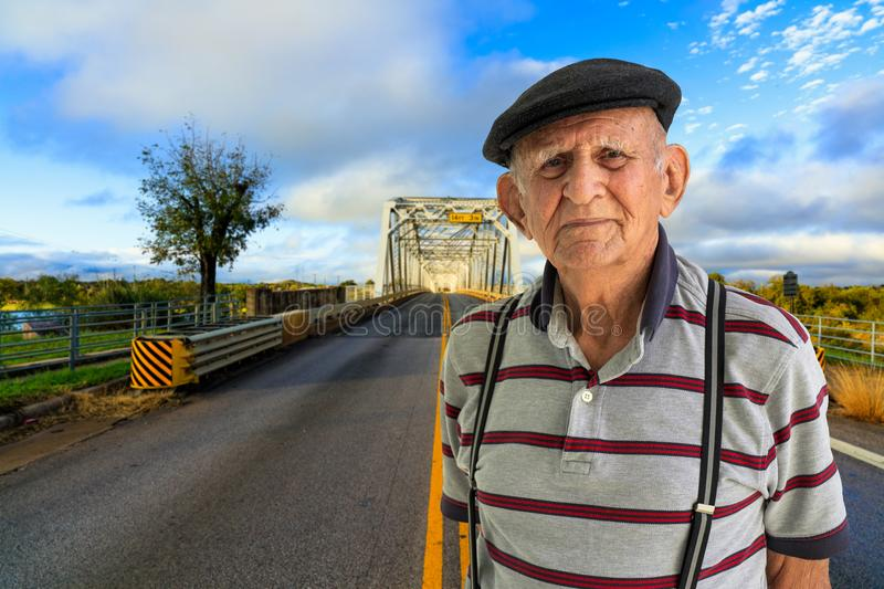 Elderly Man Outdoors. Elderly 80 plus year old man outdoor portrait standing in the road with a vintage bridge in the background royalty free stock photos
