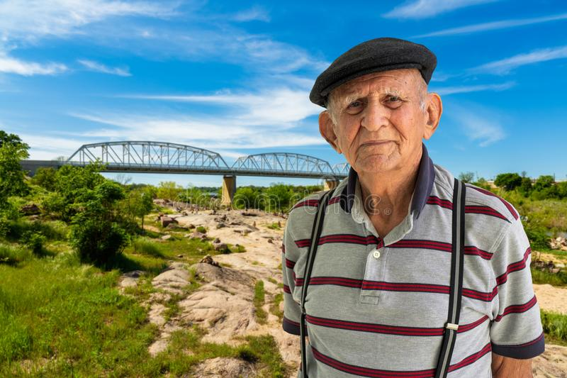 Elderly Man Outdoors. Elderly 80 plus year old man outdoor portrait with a vintage bridge in the background royalty free stock photo