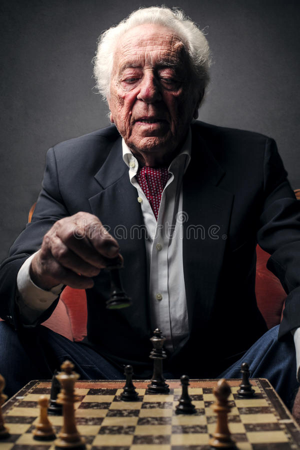 Elderly man playing chess stock photography