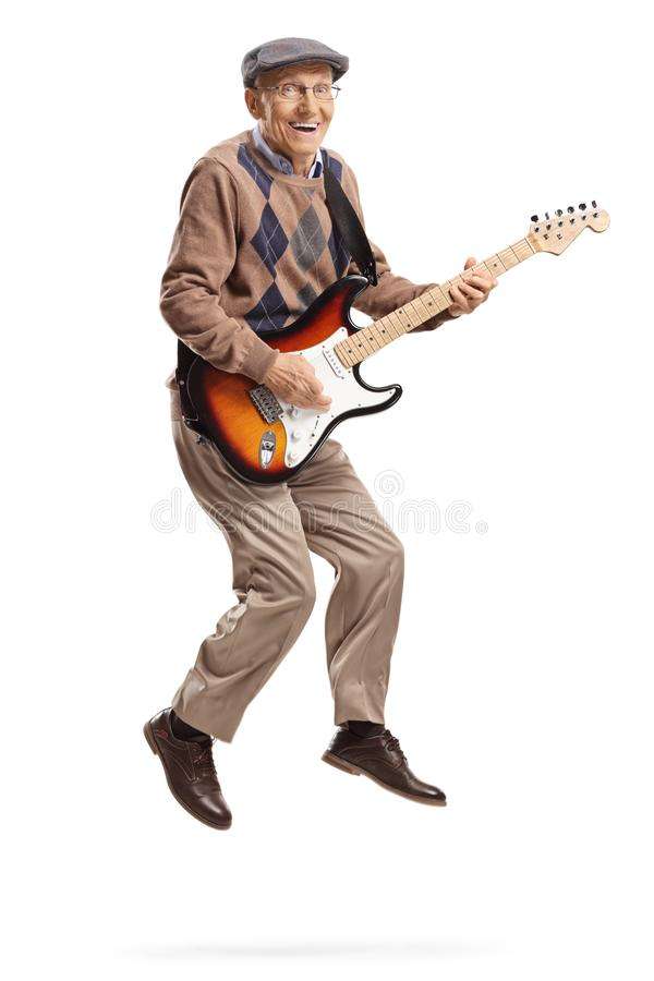Elderly man playing an electric guitar and jumping stock photos