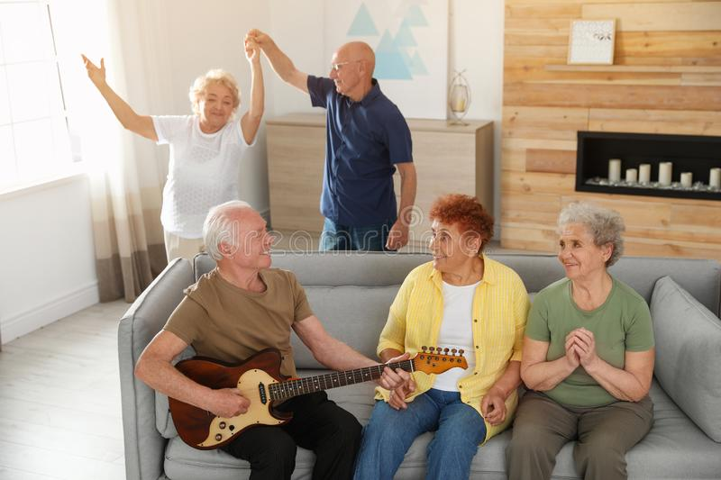 Elderly man playing guitar for his friends stock images