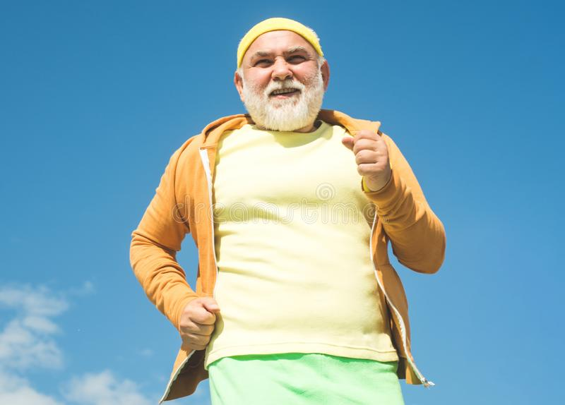 Elderly man practicing sports on blue sky background. Elderly man jogging. Golden age grandfather. Senior fitness person. Running in park for good health royalty free stock images