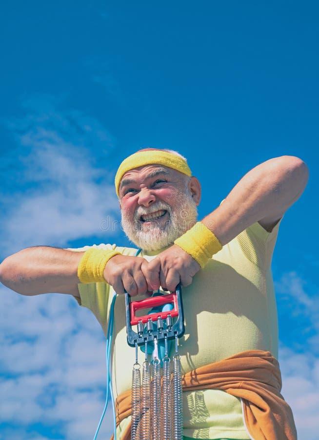 Elderly man practicing sports on blue sky background. Grandfather pensioner. Sporting. Senior sportsman in sport center. Senior man workout in rehabilitation stock photos