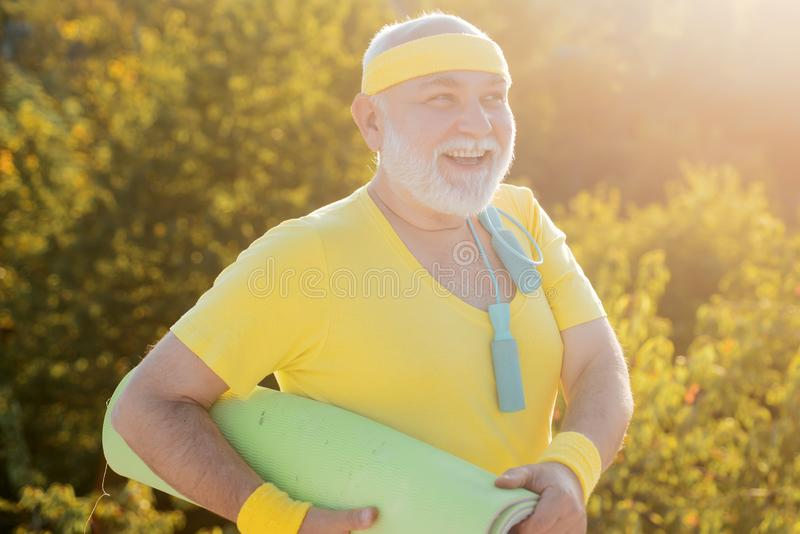 Elderly man practicing sports on blue sky background. Senior man is doing fitness training. Freedom retirement concept. royalty free stock photography