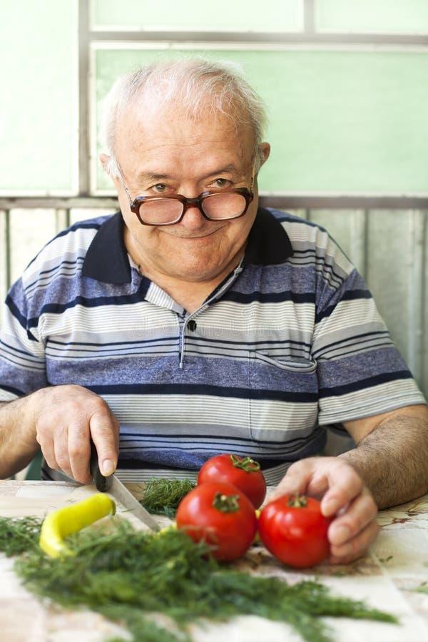 Elderly man preparing healthy food. Vegetarian diet royalty free stock photo