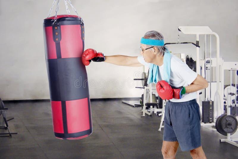 Elderly man punching a boxing bag royalty free stock photos