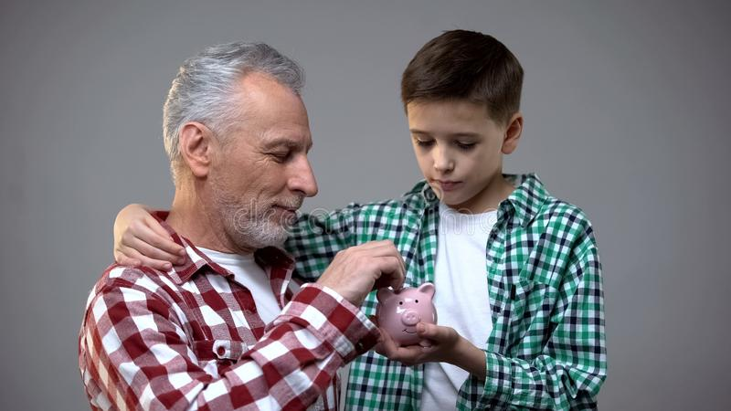 Elderly man putting coin into little boy piggy bank, savings for future, banking stock image