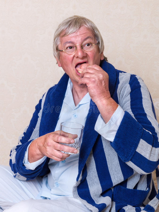 Elderly man putting dentures in stock image
