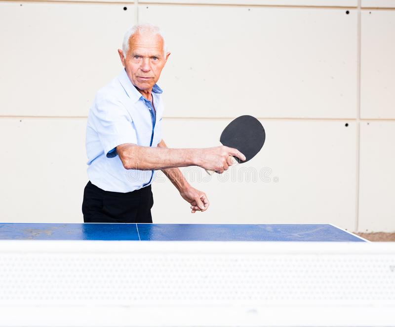 Portrait of elderly man with rackets for table tennis. Of elderly man with rackets for table tennis royalty free stock image
