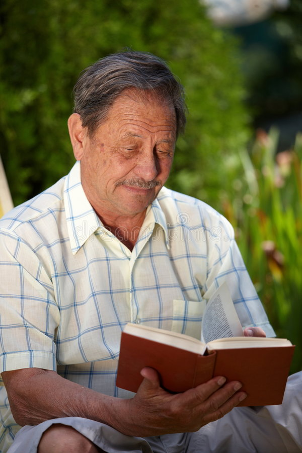 Elderly man reading book stock photo