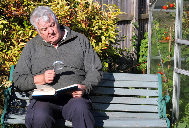 Elderly man reading with magnifying glass. royalty free stock images