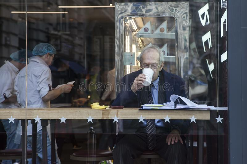 Elderly man reading a newspaper for morning coffee in a shop window stock photos