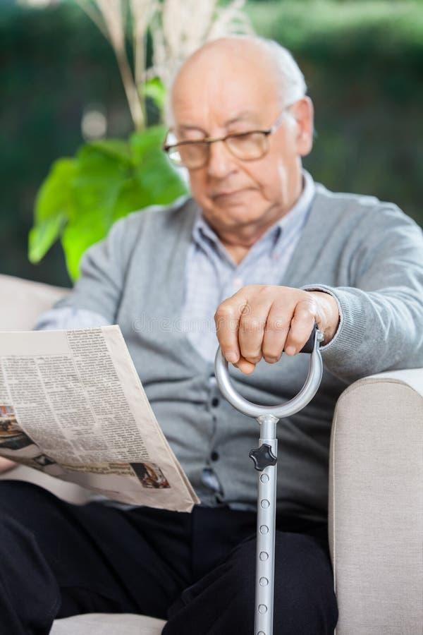 Elderly Man Reading Newspaper At Nursing Home stock photo