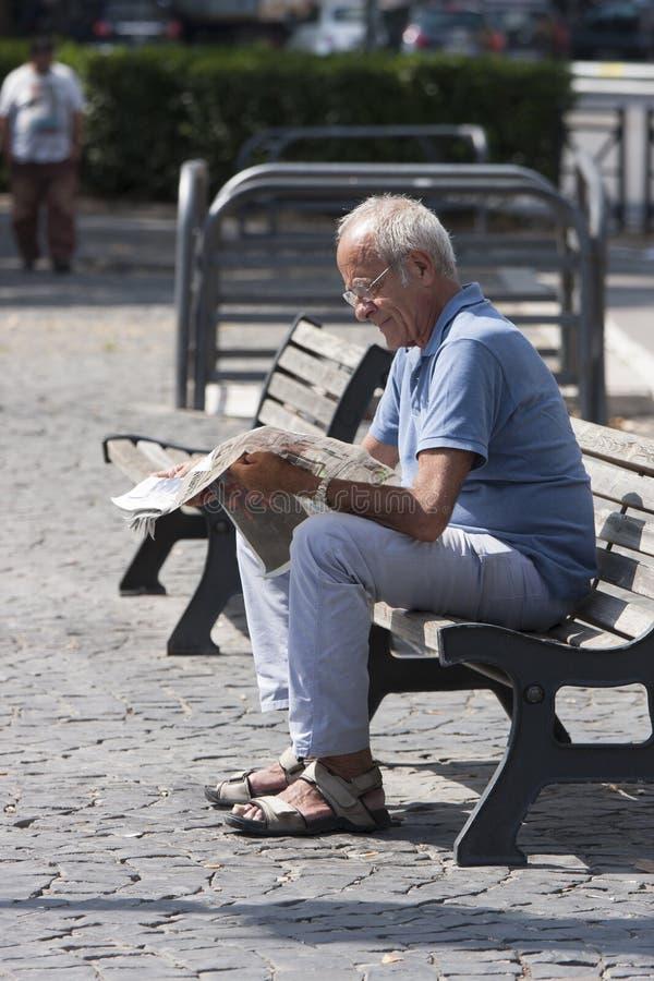 Elderly man reading newspaper royalty free stock photos