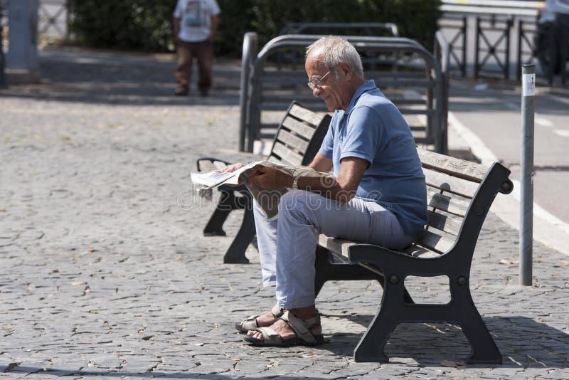 Elderly man reading newspaper stock photography