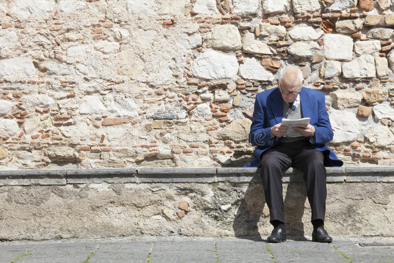 Elderly man reading and sitting on a stone bench. Stones wall royalty free stock photography