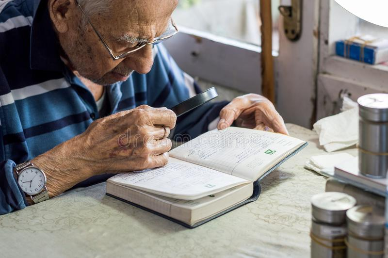 Elderly man reading writings in a notebook with magnifying glass near the window at home royalty free stock images