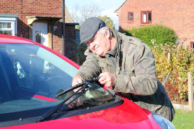 Elderly man renewing car wiper blades royalty free stock images
