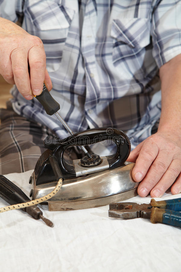 Elderly man repairing electric iron. Ancient electric iron stock images