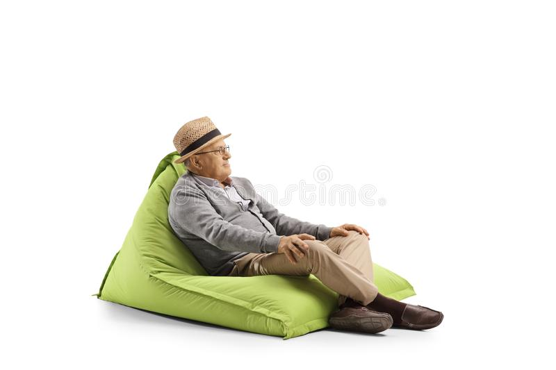 Elderly man resting on a bean-bag armchair. Isolated on white background stock photo