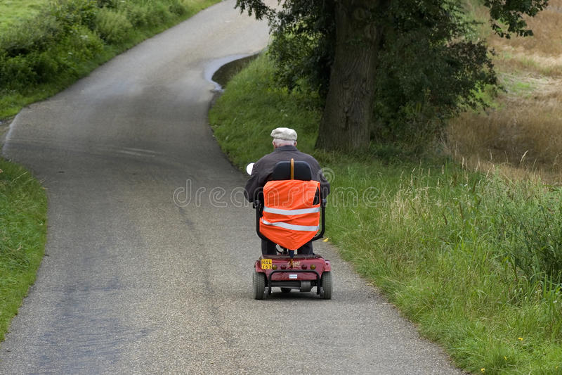 Elderly man riding mobile scooter, Netherlands. In the south of the province of Limburg it is difficult for the elderly people to remain independent mobile stock image