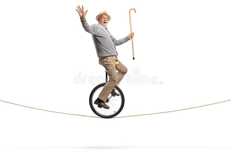 Elderly man riding a mono-cycle on a rope and holding a walking cane stock photo