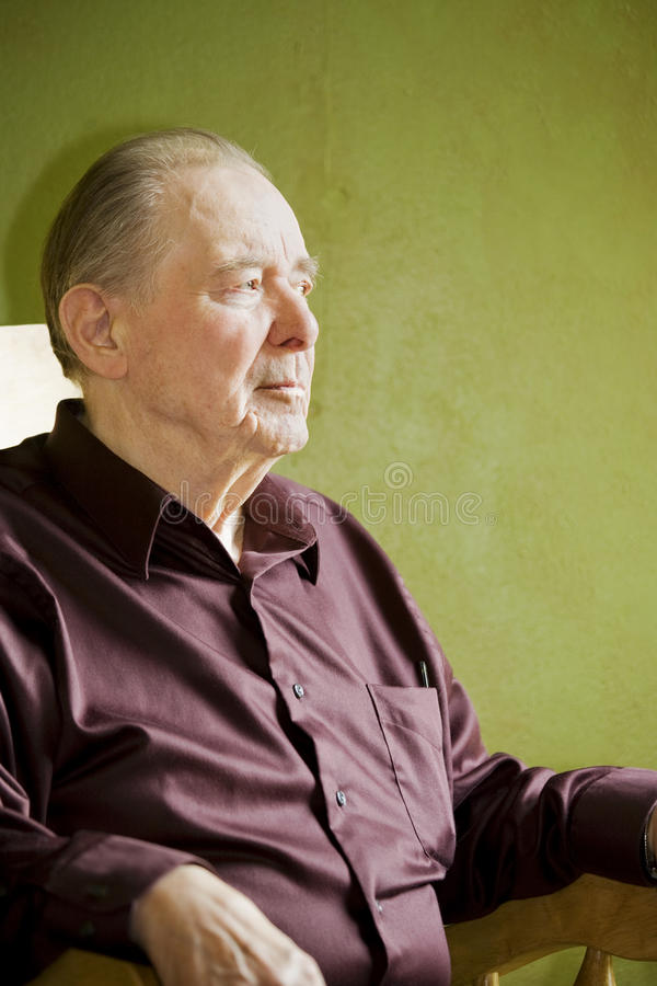 Elderly man in rocking chair stock photography