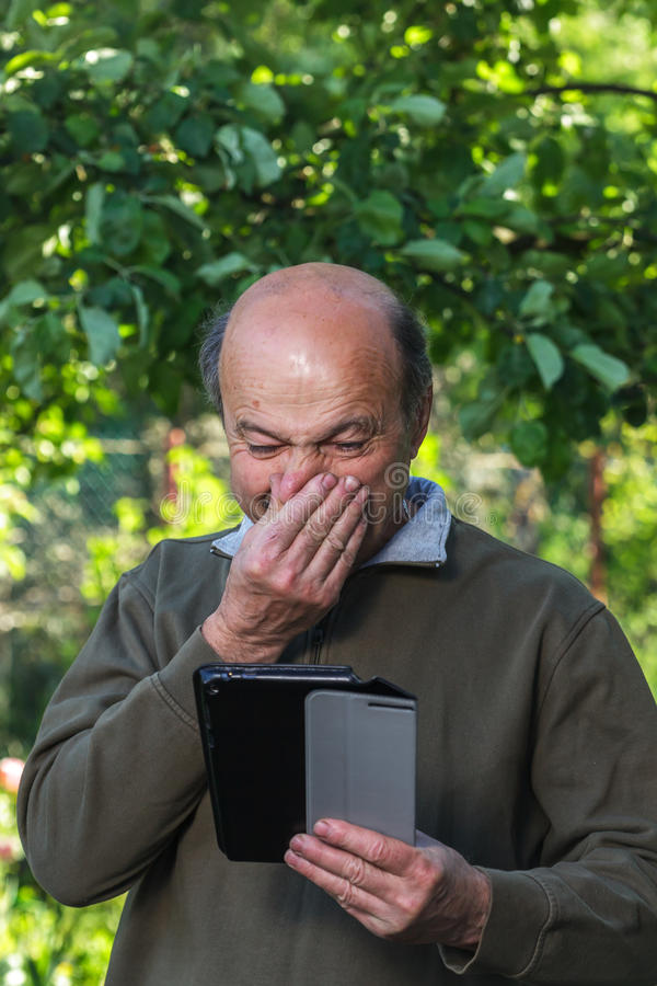 Elderly man with a runny nose looking for cure on the Internet. Elderly man with a bald head, mustache and glasses learn to deal with tablet royalty free stock photos