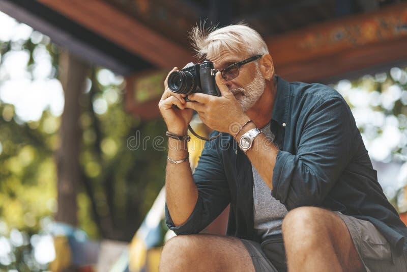 Elderly man`s hobby is photography. Retirement travel, outdoor activities. Adventures in life of senior people stock photo