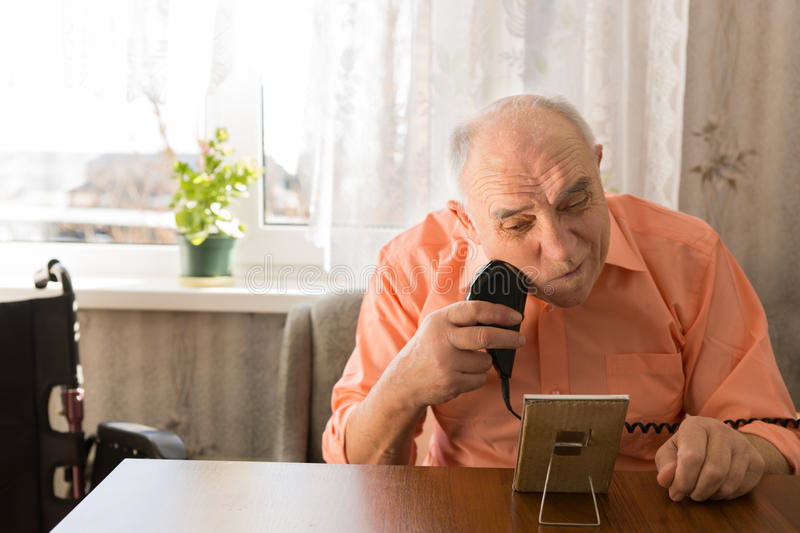 Elderly Man Shaving Beard with Razor at the Table. Close up Sitting Elderly Man Shaving Beard with Electric Razor Device at the Wooden Table Inside the House stock images