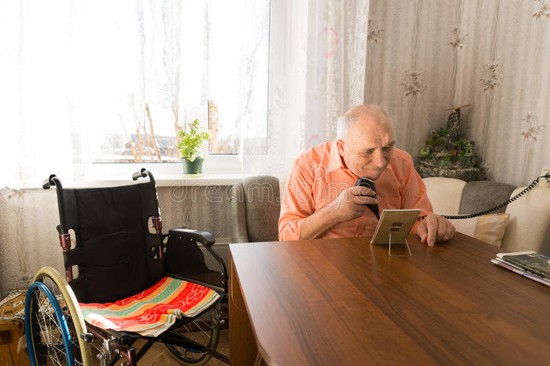 Elderly Man Shaving his Beards at the Living Room. Sitting Elderly Man Shaving Beards with Electric Razor at the Living Room with his Wheel Chair on the Side royalty free stock photo