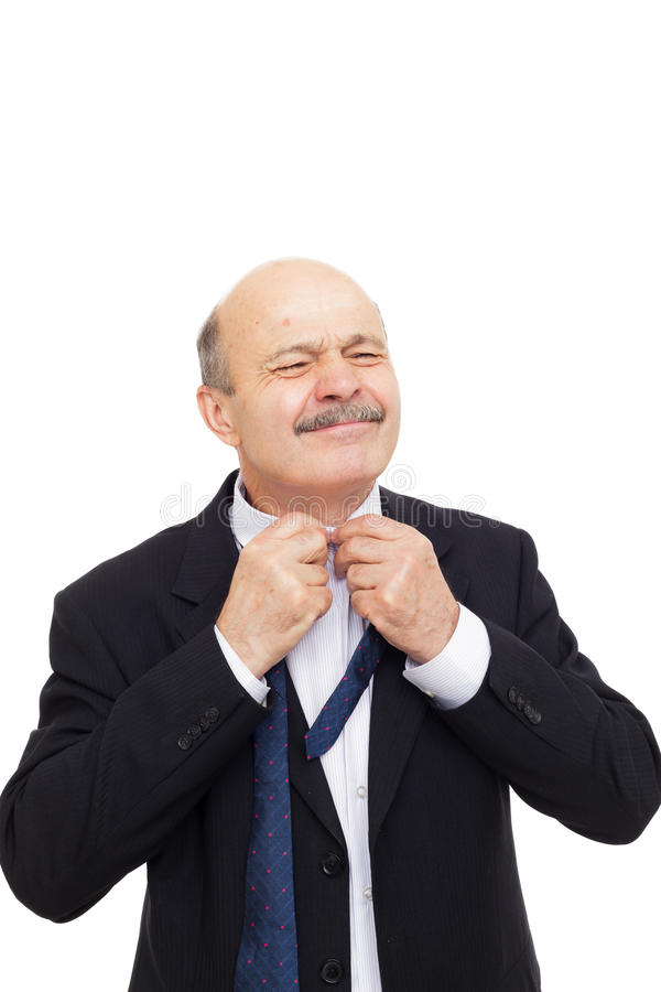 Elderly man in a shirt trying to undo a button. Man tying his tie preparing for the meeting royalty free stock photography
