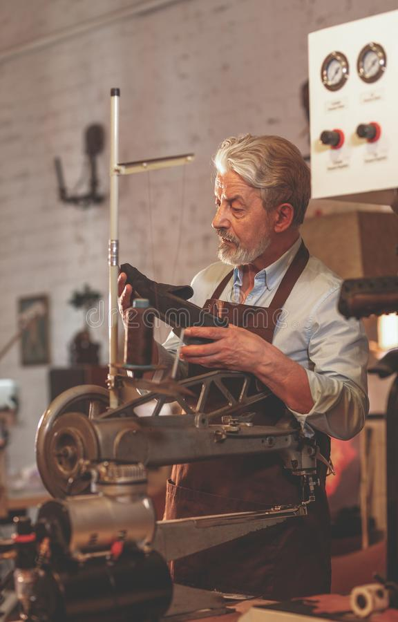 An elderly man with a shoe. In a workshop stock photos