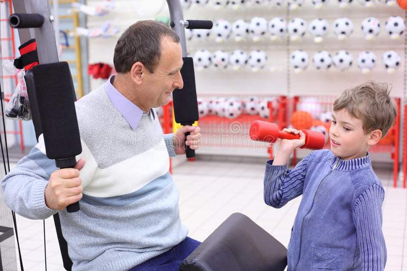 Elderly man in shop on sports exerciser and boy royalty free stock images
