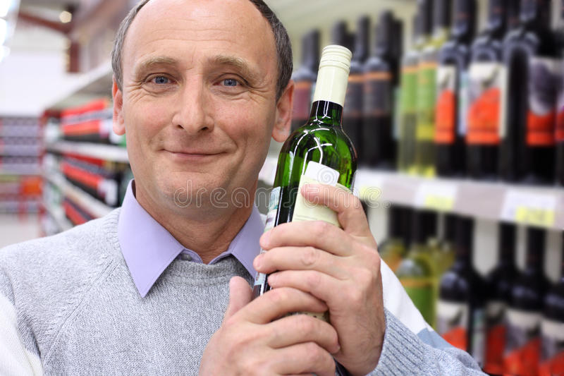 Elderly man in shop with wine bottle stock images