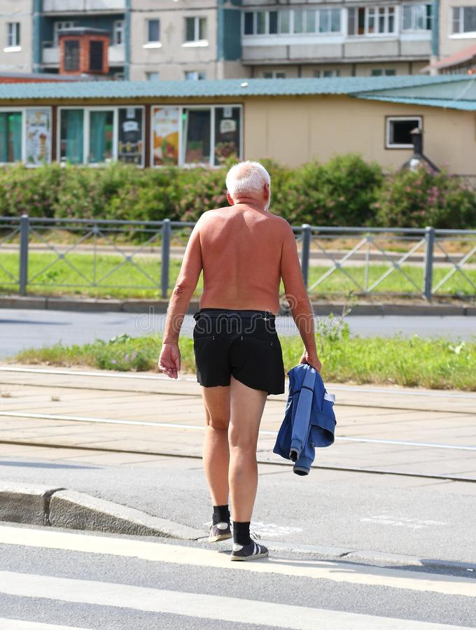 An elderly man in shorts on the street stock photography