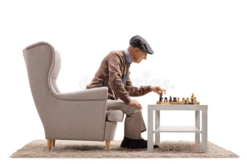 Elderly man sitting in an armchair and playing chess with himself stock photos