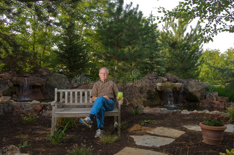 Elderly man sitting on a bench stock photography