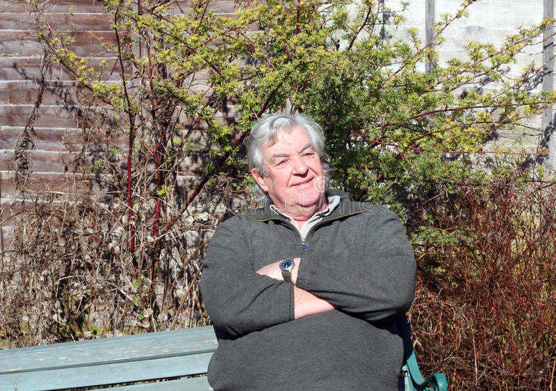 Man relaxing with folded arms. An elderly man sitting on a bench in the sunshine relaxing and smiling with his arms folded stock image